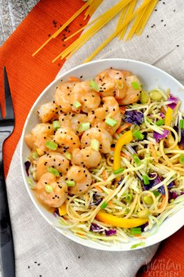 Photo of finished Thai peanut shrimp bowl taken from overhead with fork to left