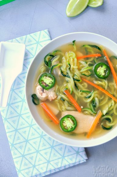 Overhead shot of Asian Chicken Vegetable Noodle Soup with white spoon to left of bowl