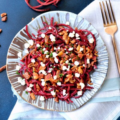 Overhead photo of beet noodle salad on plate with fork to right side
