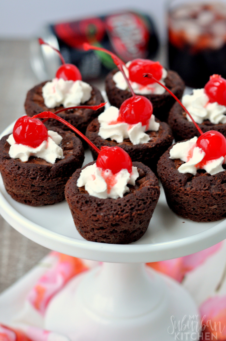 Multiple brownie bites on cupccake stand with whipped cream and cherries