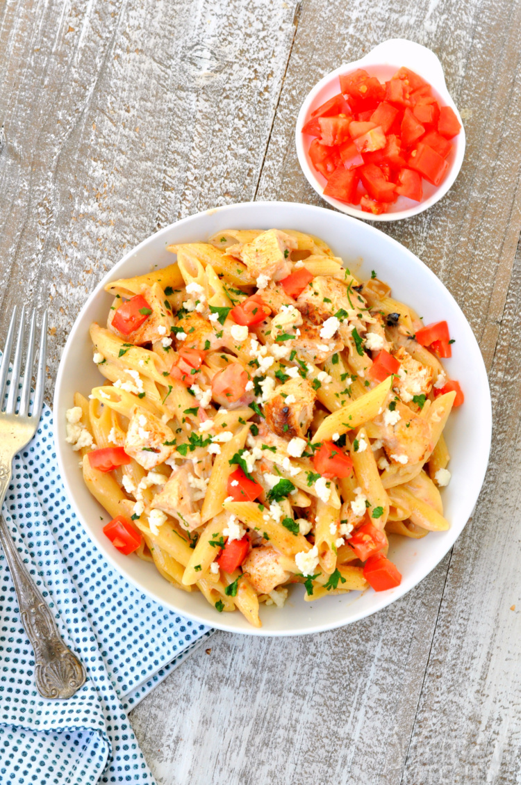 Flat lay photo of one pot taco chicken alfredo pasta with bowl of tomatoes, napkin and fork
