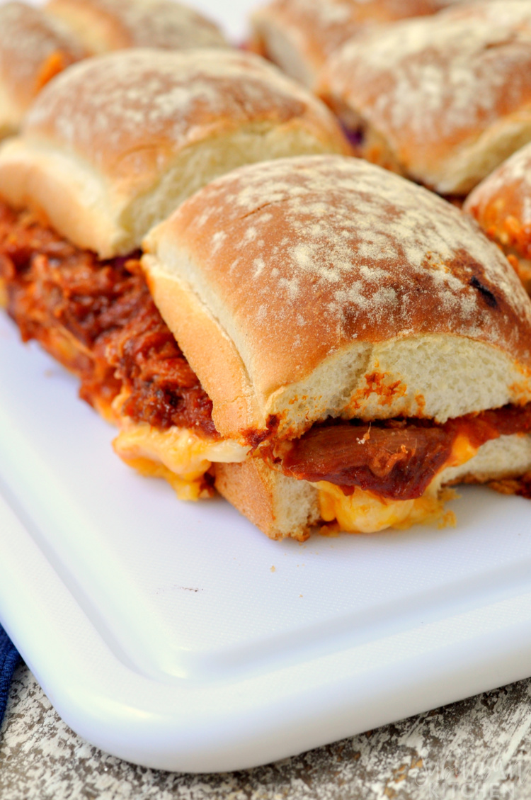 Multiple pimento cheese pulled pork sliders on white cutting board