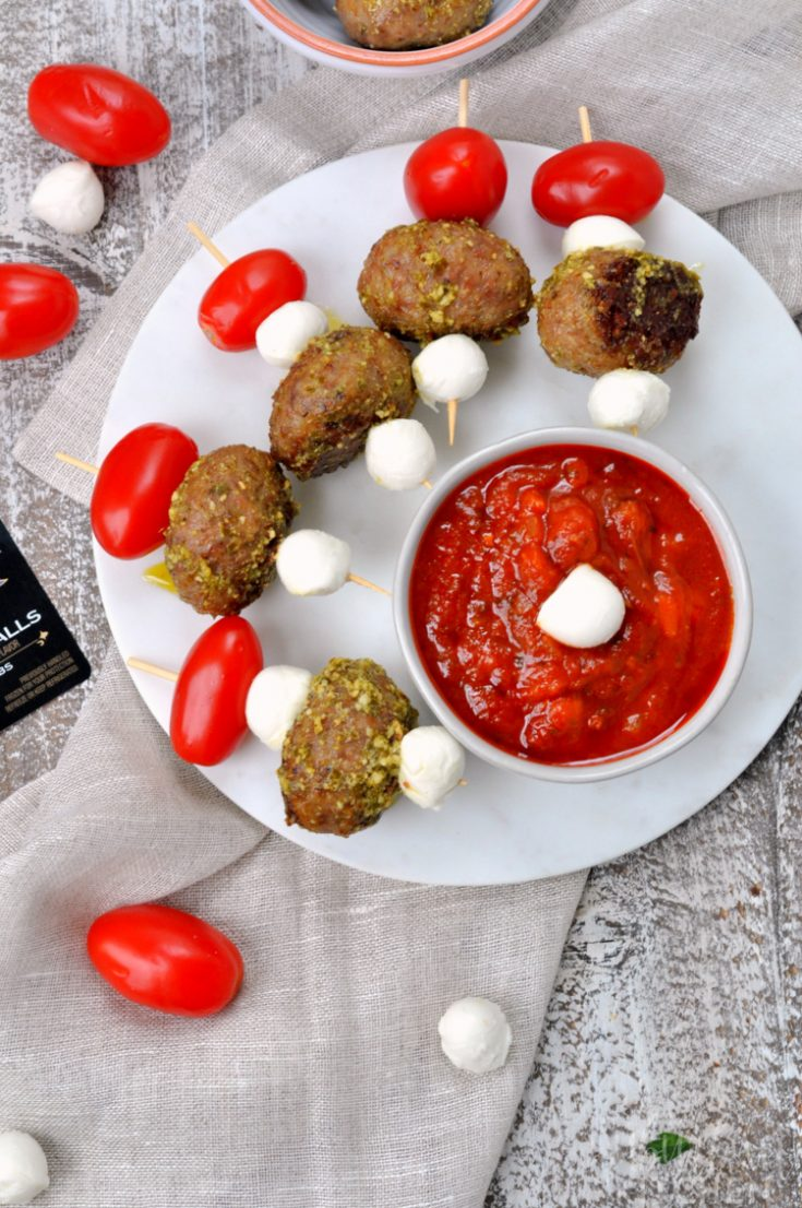 Caprese Meatball Skewers on serving platter with marinara sauce