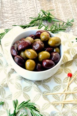 Bowl of warm marinated olives with greenery