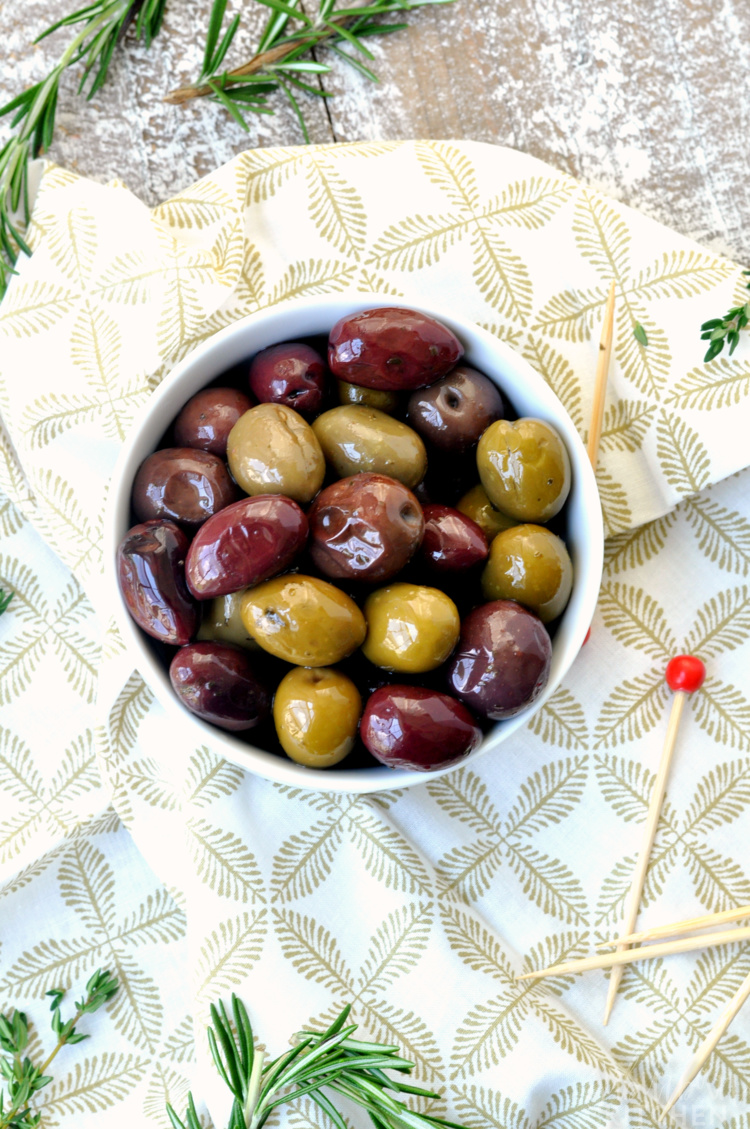 Overhead photo of marinated olives in white bowl